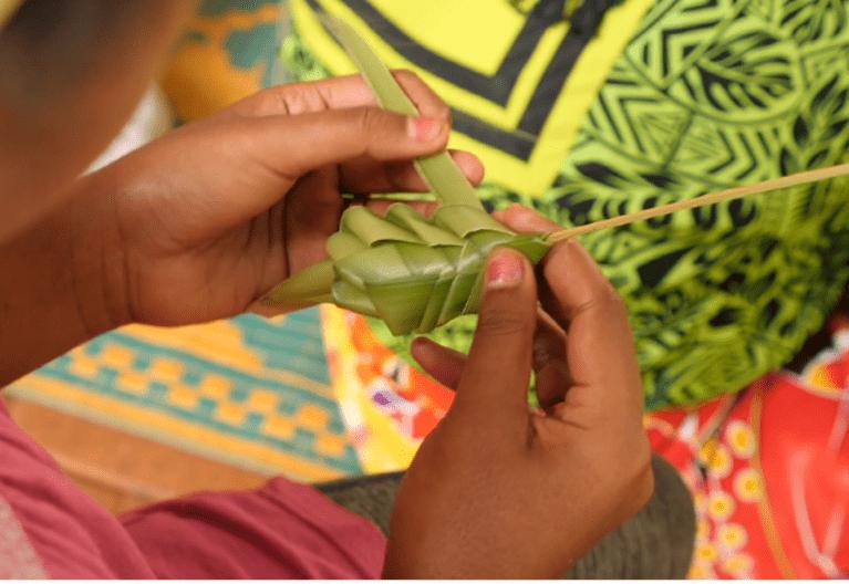 Petite fille en train de tresser avec des fibres naturelles