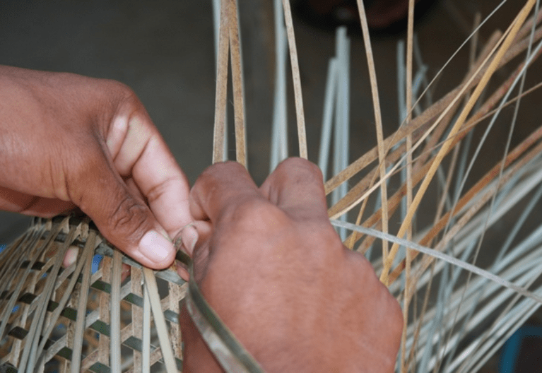 Individu Wayana en train de tisser un panier.