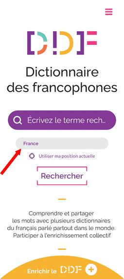 """Capture d'écran de la page d'accueil du Dictionnaire des francophones. Tout en haut de la page, à droite, se situe un bouton constitué de trois traits roses, permettant d'afficher le menu. Egalement, en haut de la page, se trouve le logo du Dictionnaire des francophones. Au milieu, il y a une barre de recherche et une zone où il est possible d'indiquer sa position, soit en l'écrivant, soit en cliquant sur """"utiliser ma position actuelle"""". Cette zone est mise en évidence par une flèche rouge. Juste en dessous, il y a un bouton avec la mention """"Rechercher"""". Il y a également le petit texte """" Comprendre et partager les mots avec plusieurs dictionnaires du français parlé partout dans le monde. Participer à l'enrichissement collectif"""". Enfin, tout en bas de la page, il y a un demi-cercle jaune où il est écrit """"Enrichir le DDF""""."""