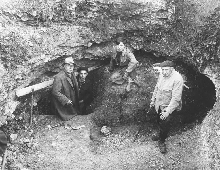 Entrée de la grotte partiellement déblayée. De gauche à droite, Léon Laval, Marcel Ravidat, Jacques Marsal et l'abbé Breuil.