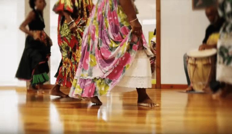 Femmes dansant le gwoka qui portent des joupes fleuries. Détail sur leurs jambes en mouvement.