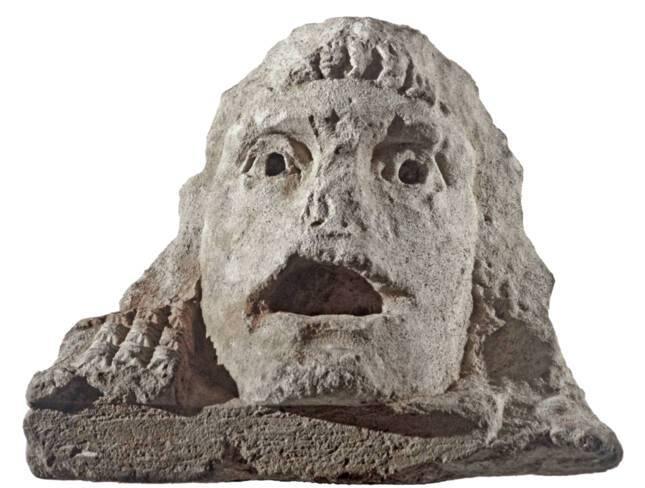 Vue rapprochée d'un acrotère en pierre en forme de masque de théâtre, représentant un adolescent, découvert dans le puits à dromos LX à Glanum.