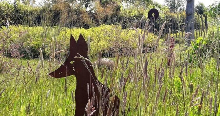 Vue sur des fourrés et silhouette d'un chien en fer