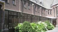 Vue de la cour intérieure, une verrière adossée sur la façade gauche et jonchée de plante