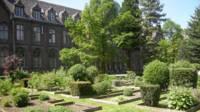 Jardin structuré au premier plan, université catholique de Lille au second