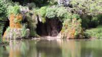 Etang au premier plan, à l'arrière plan une grotte qui surplombe l'étang