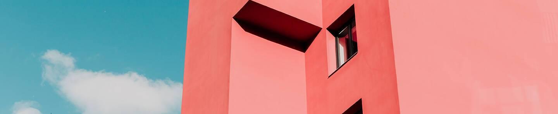 Devanture d'un immeuble moderne de couleur rosée sur fond de ciel bleu