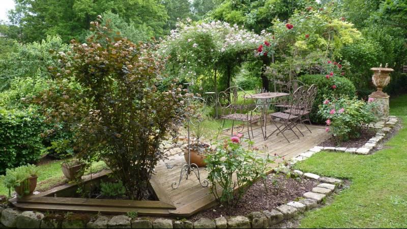 Table et chaises de jardin au milieu d'un bosquet