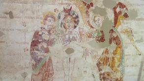 Cette peinture murale représentant le baptême du Christ date du XIIe siècle tandis que le décor ornemental de double faux joints rouge daté du XIIIe siècle